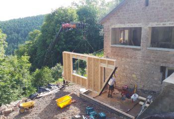 Extension en bois d'une maison en pierre levage façade