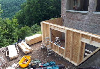 Extension en bois d'une maison en pierre pose façade